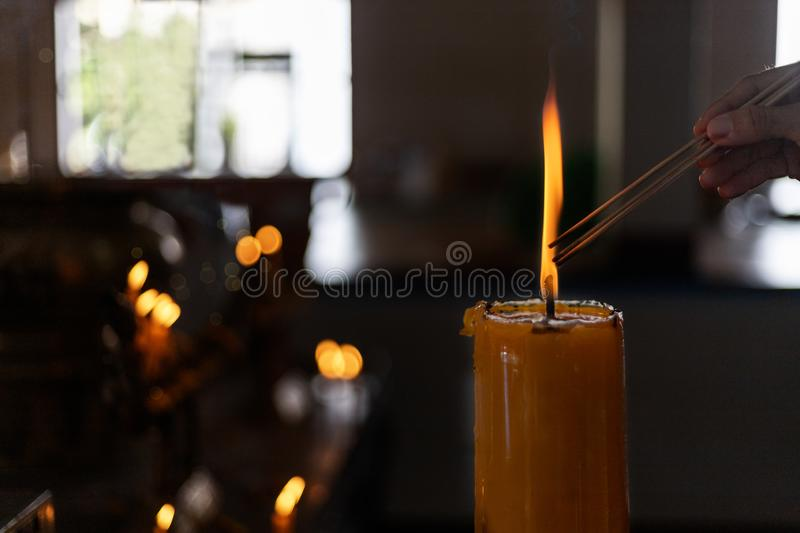 Buddhist Lent concept. Women hand lighning the incense from big candles in the Buddhist temple Close up light form candles. Process with low key style. With royalty free stock image