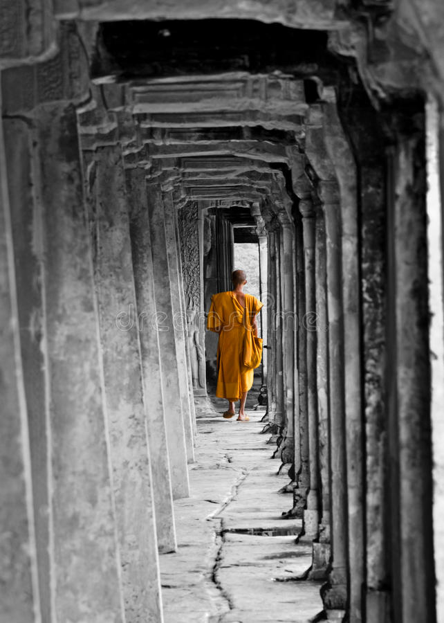 Buddhist Monk at Angkor Wat, Cambodia. Buddhist Monk at Angkor Wat Monastry, Cambodia, black and white/orange royalty free stock images