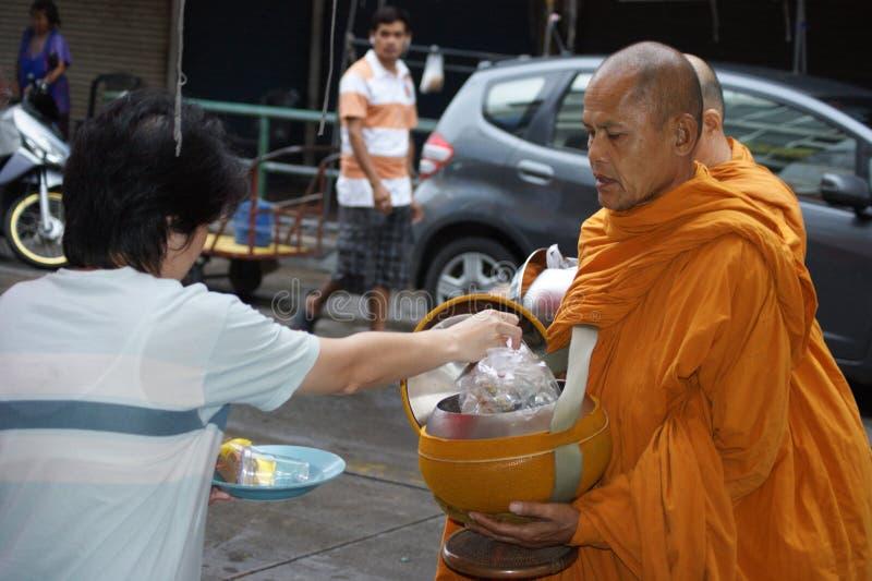 Buddhist monks alms on Bangkok`s streets stock images
