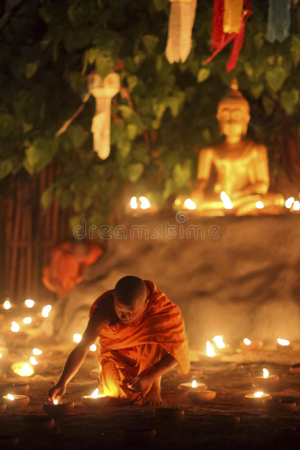 Buddhist monk fire candles to Buddha royalty free stock photography
