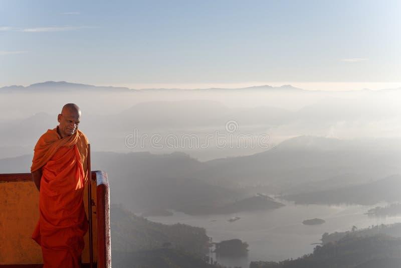 Buddhist monk meets pilgrims, Adams Peak, Sri Lanka. Sri Lanka, Southern Asia - February 14, 2015: Buddhist monk meets sunrise with pilgrims on the mountain royalty free stock photo