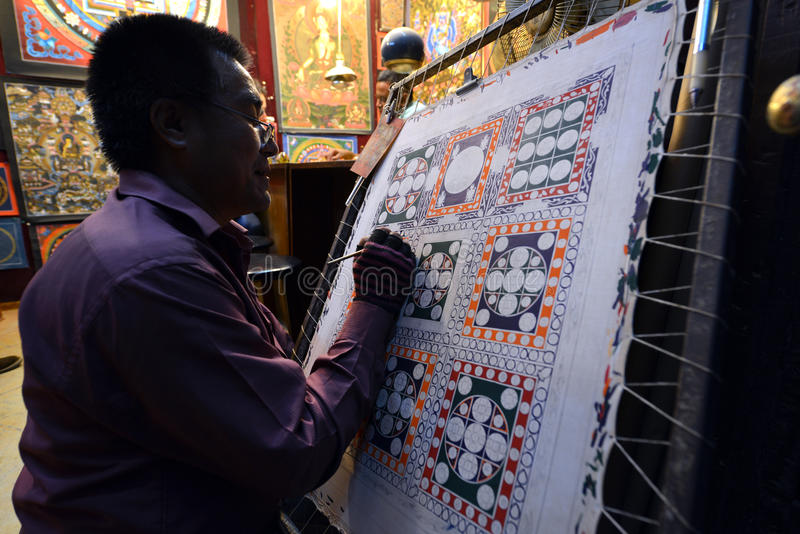 Buddhist monk paints a painting. PATAN, NEPAL – SEPTEMBER 28: Buddhist monk paints a circular Budhhist painting in Patan. On September 28, 2013, in royalty free stock photo