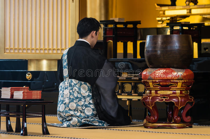 Buddhist monk praying in temple in Tokyo royalty free stock image
