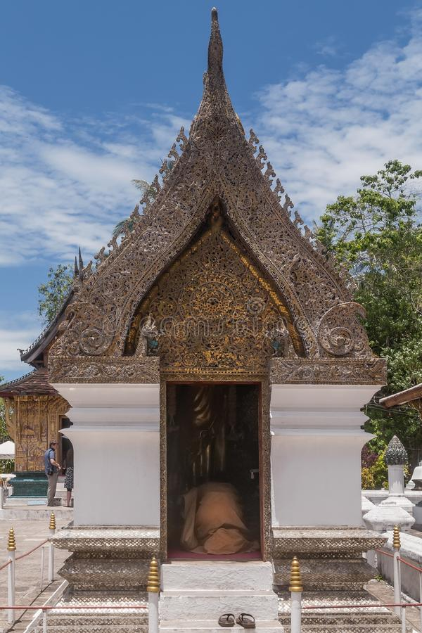 Buddhist monk prays kneeling in a shrine inside the Wat Xieng Thong temple in Luang Prabang, Laos. Asia stock image