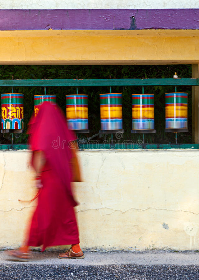 Buddhist monk rotating prayer wheels stock photography