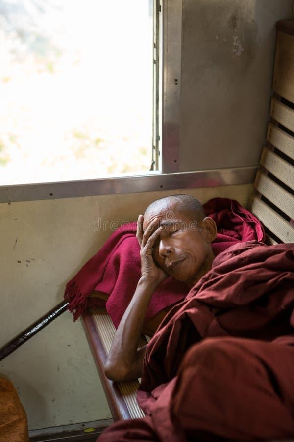 Buddhist monk sleeps on wooden train seat. stock images