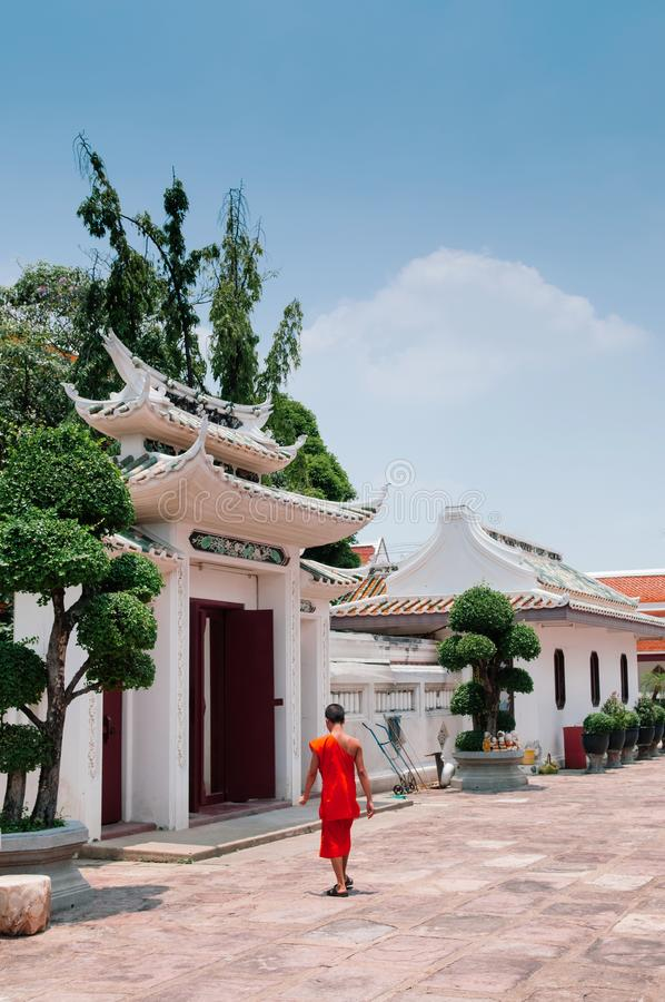Buddhist monk walking pass the gate of Wat Ratchaorotsaram Bang royalty free stock photography