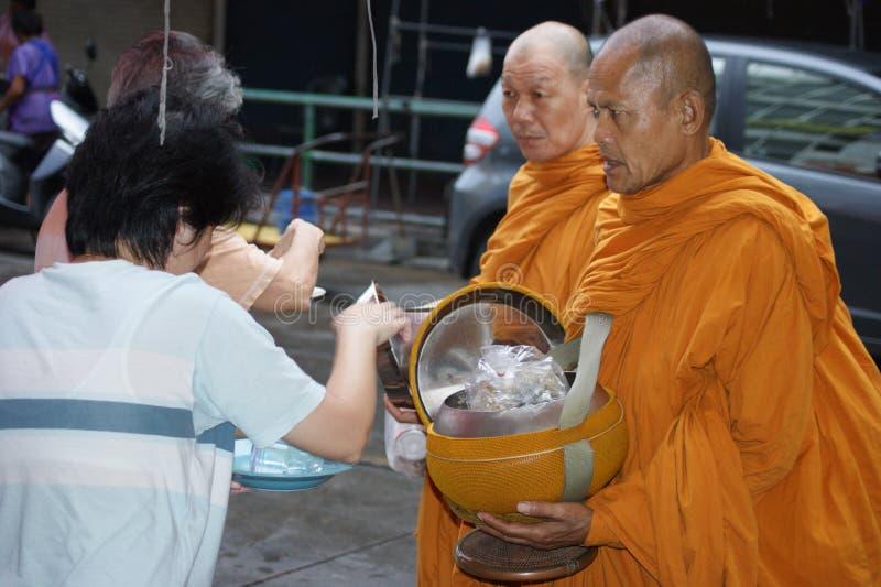 Buddhist monks alms on Bangkok`s streets royalty free stock photography