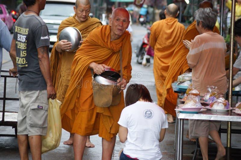 Buddhist monks alms on Bangkok`s streets royalty free stock photo