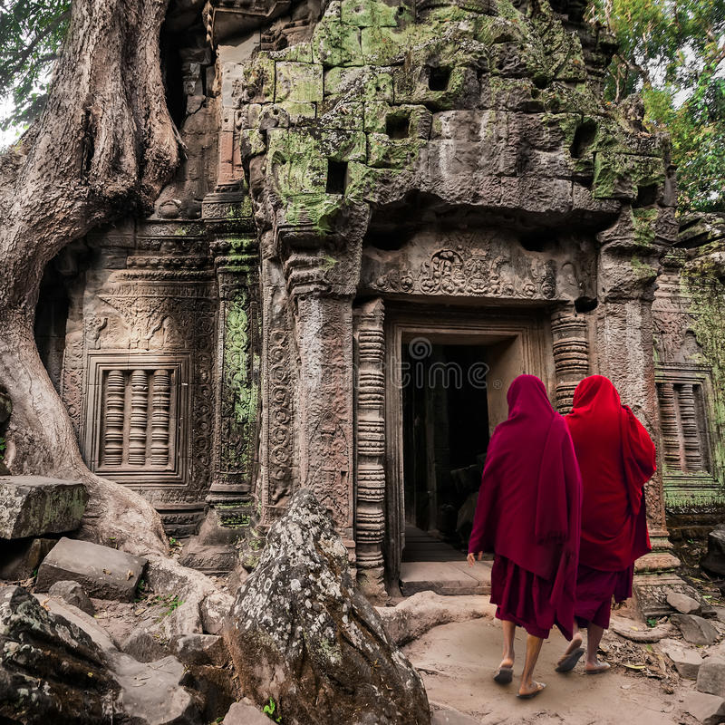 Buddhist monks at Angkor Wat. Siem Reap, Cambodia. Buddhist monks at Angkor Wat. Ancient Khmer architecture, Ta Prohm temple ruins hidden in jungles. Popular royalty free stock image