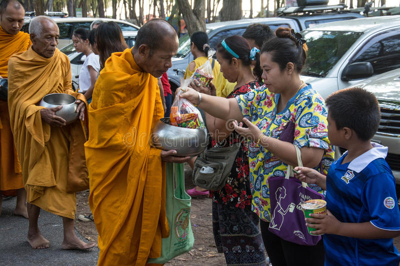 Buddhist monks are given food offering from people for Songkran day or Thai New Year Fe. Prachuap Khiri Khan, THAILAND - APRIL 13 : Buddhist monks are given food royalty free stock image