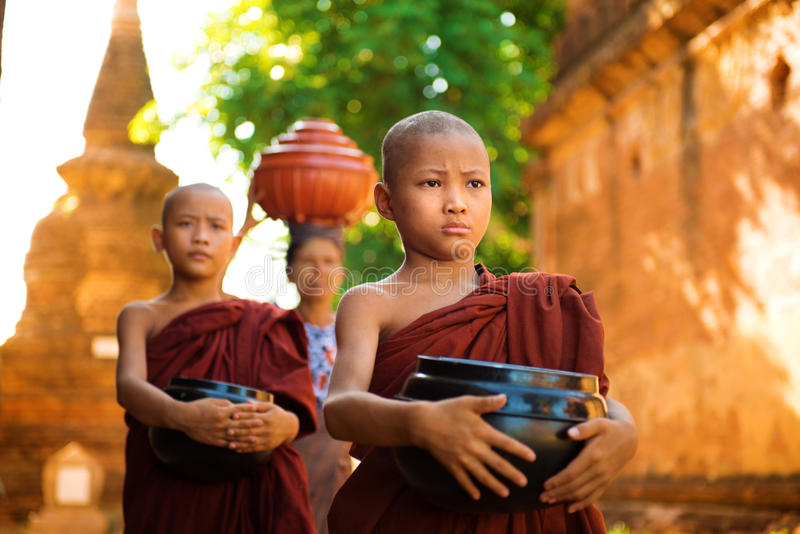 Buddhist monks Myanmar. Young Buddhist monks walking morning alms in Old Bagan, Myanmar stock images