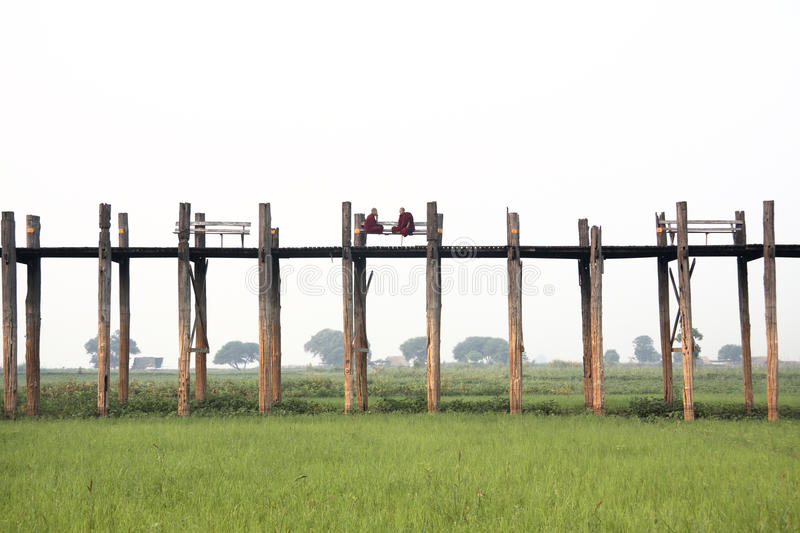 U Bein Bridge, Mandalay, Myanmar with Buddhist monks on U Bein Bridge stock photo