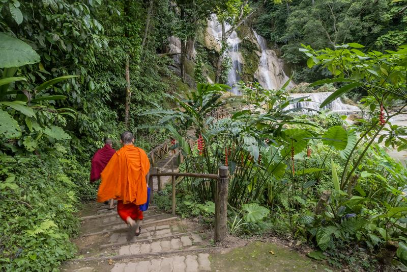 Buddhist monks visiting the Kuang Si waterfalls, near Luang Prabang, Laos royalty free stock photos