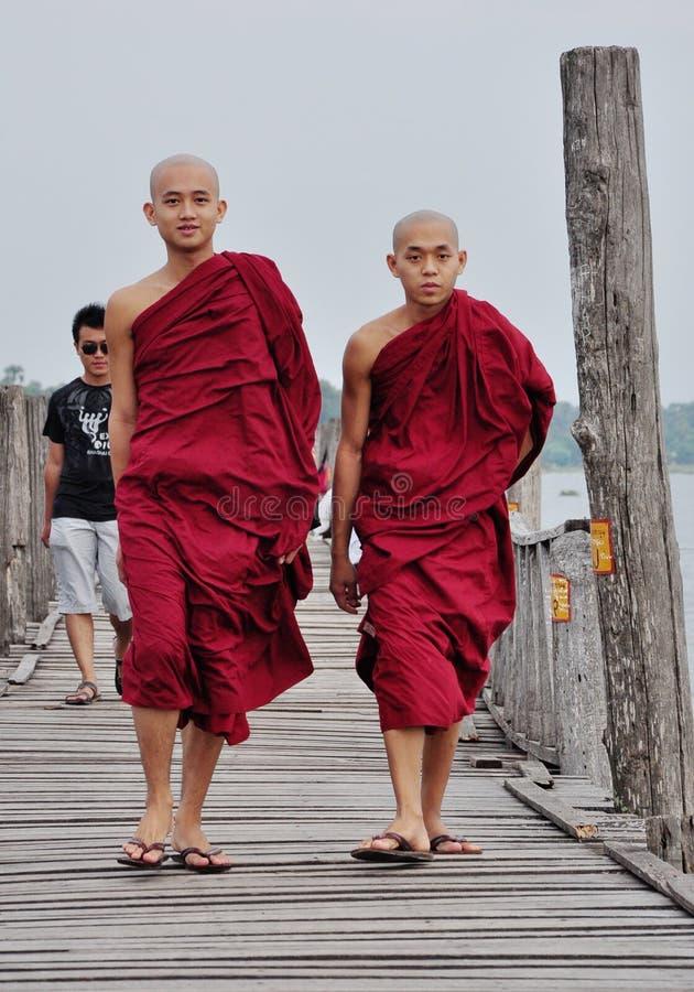 Buddhist monks walking on wooden bridge in Bagan, Myanmar.  stock image