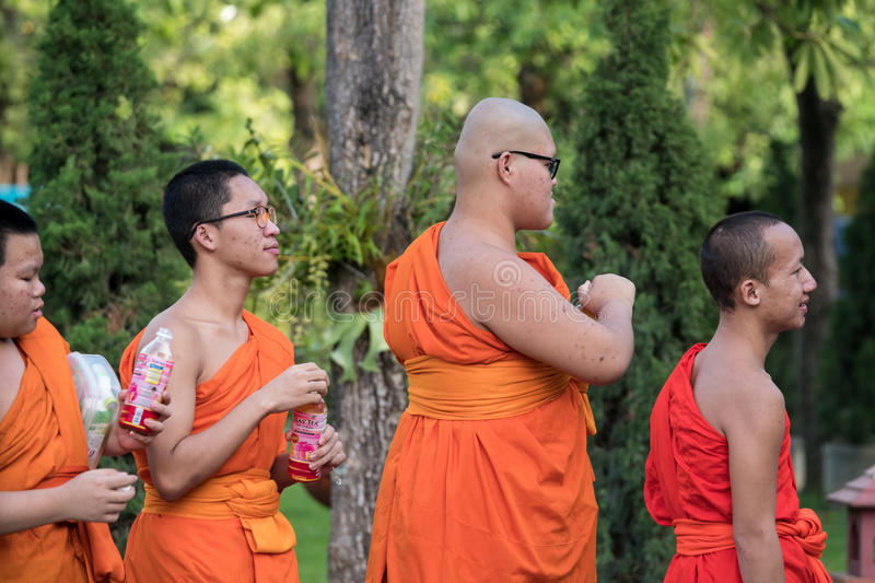 Buddhist Monks at Wat Prasing, Chiang Mai, Thailand. CHIANG MAI, THAILAND - OCTOBER 15 2016: Young buddhist monks mourn the death of their King - Bhumibol stock photos