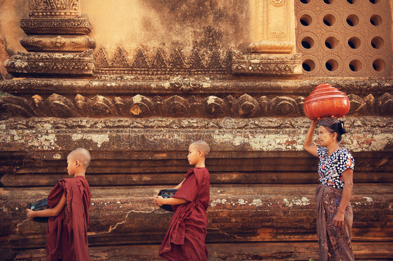 Buddhist novice monks collect alms. Buddhist novice monks walk to collect alms and offerings at old bagan, Myanmar. This procession is held every morning stock images