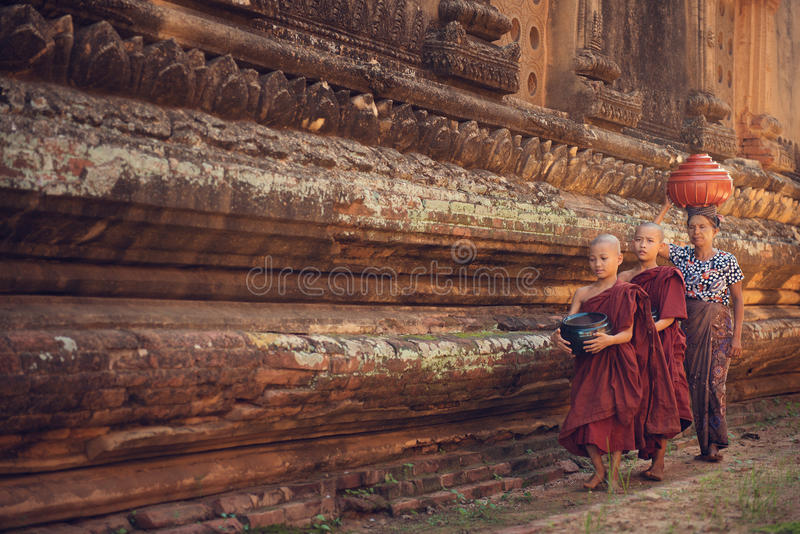 Buddhist novice monks walking alms. Young Buddhist novice monks walking morning alms in Old Bagan, Myanmar stock photos