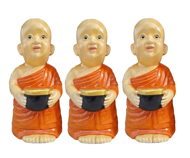 Buddhist novice resin characters holding alms bowl in hand isolated on white background stock image