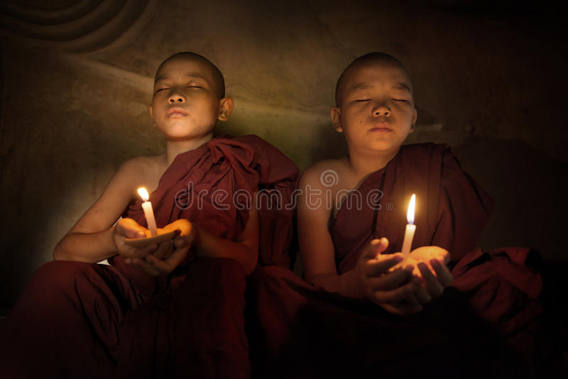 Buddhist novices praying with candlelight. Little monks praying with candlelight royalty free stock photos