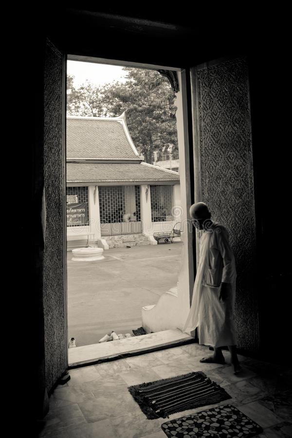 A Buddhist nun stands in a doorway of a temple in Bangkok, Thailand royalty free stock photography