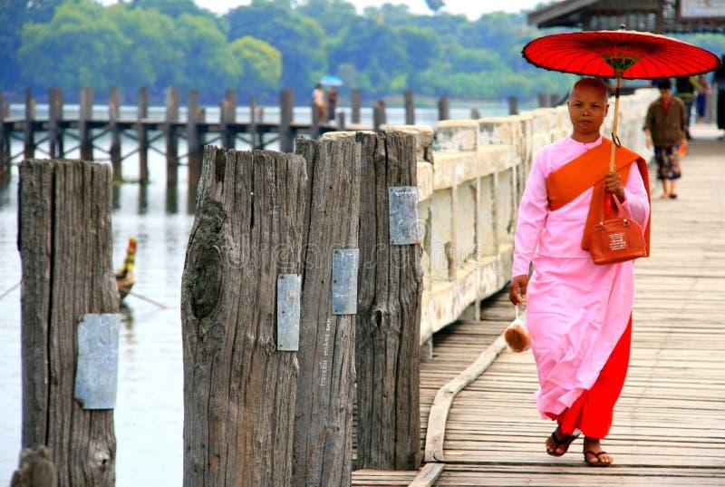 Buddhist nun walking across the U Bein Bridge, Myanmar stock photo