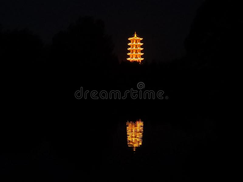 Buddhist pagoda and the invert shadow in the evening. Buddhist pagoda is circled by the light in the evening. The invert shadow is beautiful in river stock image