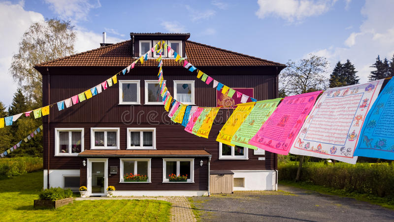 Buddhist Prayer Flags. Colourful Buddhist prayer flags flying outside a Buddhist cultural centre. Bockswiese, Harz, Germany stock image