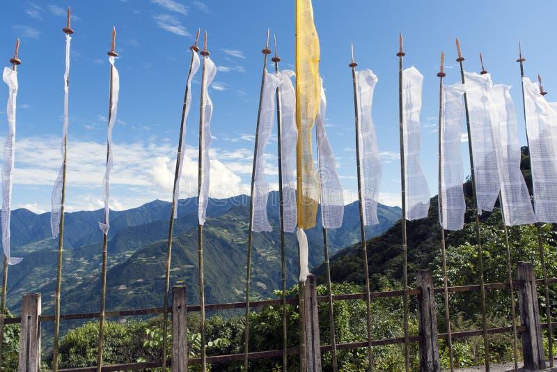 Buddhist Prayer Flags with mountains background - Bhutan. Buddhist Prayer Flags on a road bridge in the mountains near Trashigang - Eastern Bhutan stock photo