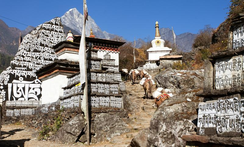 Buddhist prayer mani walls with stupa. Prayer flag and caravan of mules, way to Everest base camp, way from Lukla to Namche Bazar, Nepal royalty free stock image