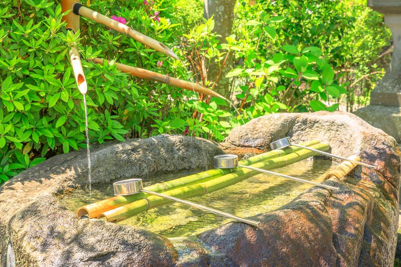 Buddhist purification fountain. Japanese Buddhist bamboo fountain with three ladles at a Buddhist temple. Hase-dera in Kamakura, Japan. Japanese culture concept stock photography