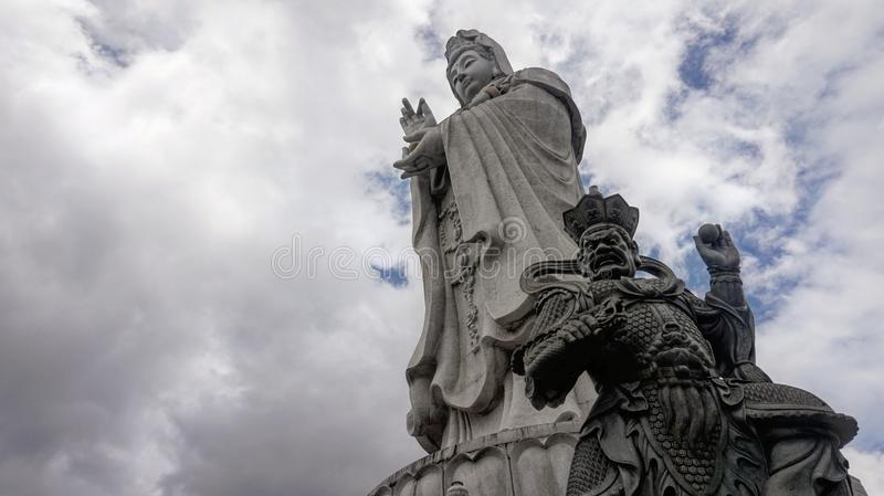 Buddhist sculpture against cloudy skies stock photos