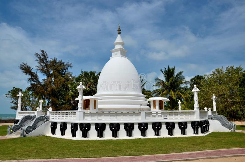 Buddhist stupa with Buddha statue at the Dambakola Patuna Sangamitta Temple complex Jaffna Sri Lanka. Jambukola, Sri Lanka - February 19, 2017: A white Buddhist stock photo