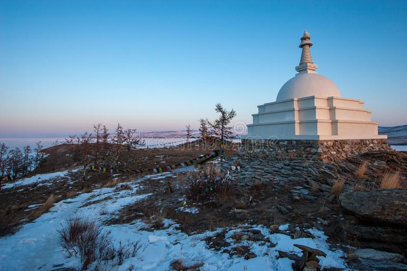Buddhist stupa on the island of Ogoy on Lake Baikal on a background of blue sky in winter. stock image
