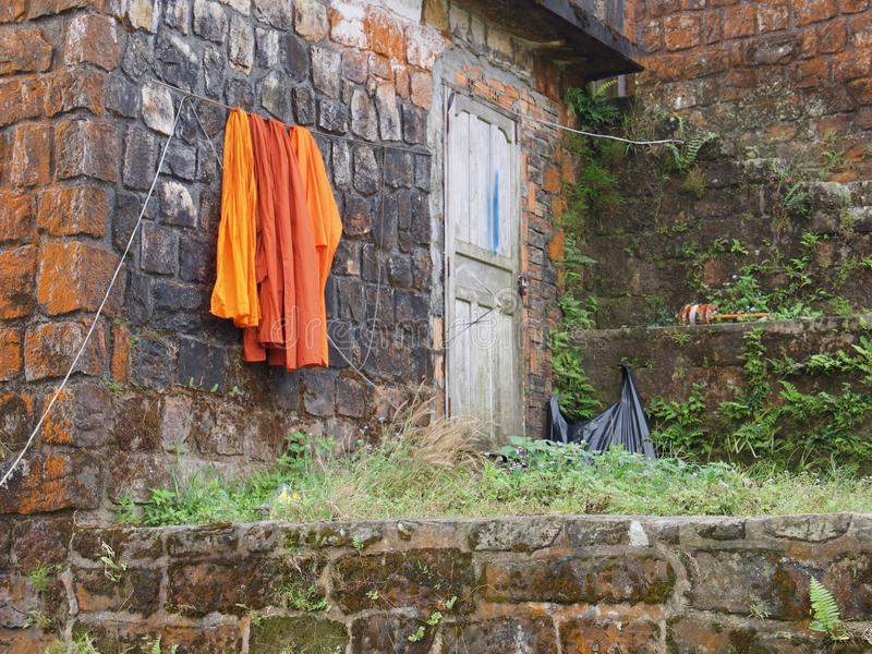 Buddhist temple with drying orange cassock. Buddhist tradition concept. Wat Sampov Pram, Preah Monivong Bokor National Park, Kampot, Cambodia royalty free stock images