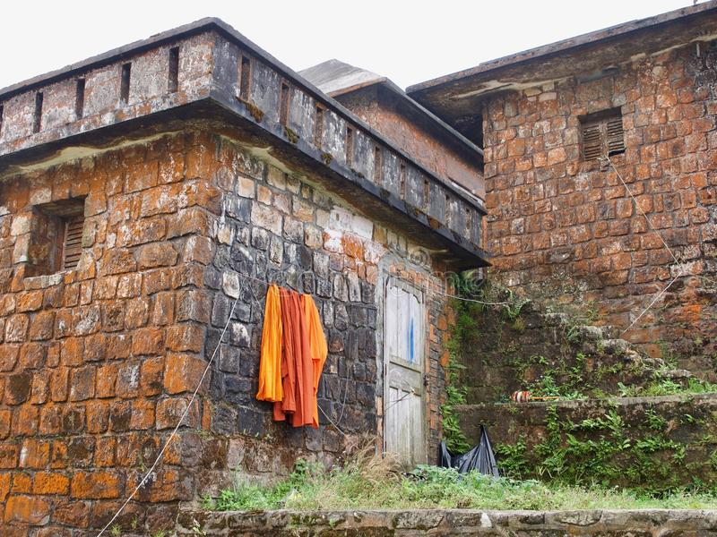 Buddhist temple with drying orange cassock. Buddhist tradition concept. Wat Sampov Pram, Preah Monivong Bokor National Park, Kampot, Cambodia royalty free stock photo