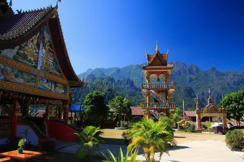 Buddhist temple with karst mountains - Vang Vieng, Laos. Buddhist temple with karst mountains against blue sky stock photos