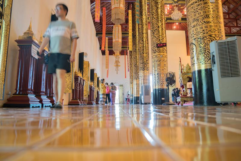 Buddhist temple low point of view long exposure. CHIANG MAI, THAILAND - JANUARY 26, 2017; People blurred in motion moving inside Buddhist temple low point of royalty free stock photography