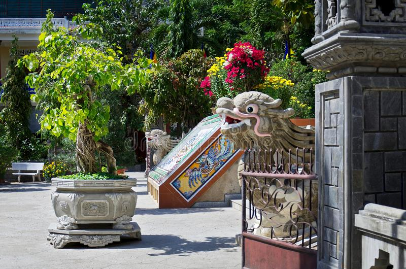 Buddhist temple in south Vietnam. Long Son Pagoda. Oriental garden with vibrant flowers and trees. glass-ceramic mosaic depicting. A dragon and dragon royalty free stock photography