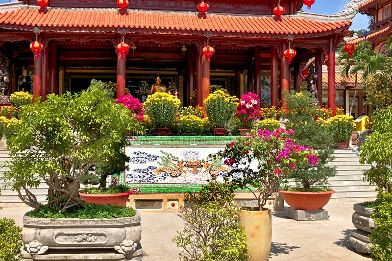 Buddhist temple in south Vietnam. Long Son Pagoda. Oriental garden with vibrant flowers and trees. glass-ceramic mosaic depicting. A dragon and dragon royalty free stock photo