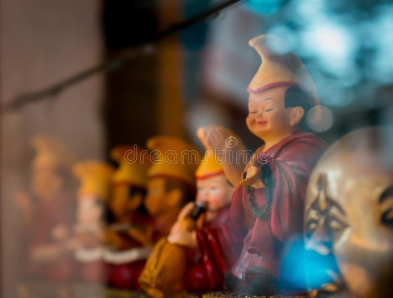 Buddhist Toys Happy Faces. Buddhist Statue toys showing through a glass reflection.Happy Luck toys buddha asia art style design asian culture monk lotus cartoon royalty free stock images