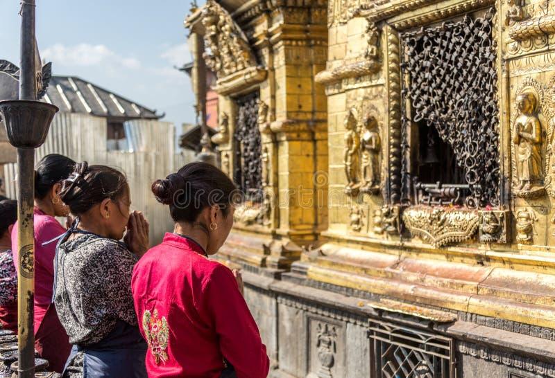 Women praying  at SWAYAMBHUNATH STUPA , the Monkey Temple, in Kathmandu, Nepal. Buddhist women praying  at the Monkey Temple,Swaymbhunath Stupa, at Kathmandu royalty free stock photos