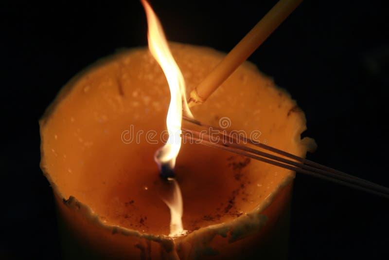Buddhisten machen den Verdienst und setzen eine brennende Kerze und einen beleuchteten Weihrauch mit Kerzenrahmen am Tempel stockbild