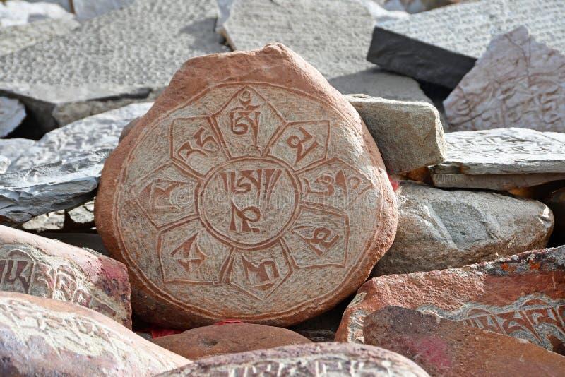 Buddhistische Gebetssteine mit tibetanischen Aufschriften und Ritualzeichnungen auf der Spur von der Stadt von Dorchen um den Kai stockfotos