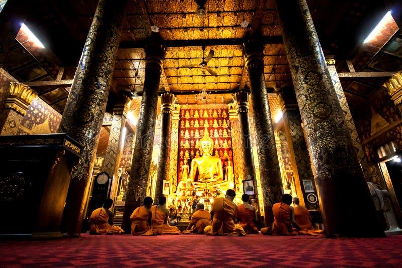 Buddhistische Mönche, die in Wat Mail während La Vesak Luang Prabang beten stockfotos