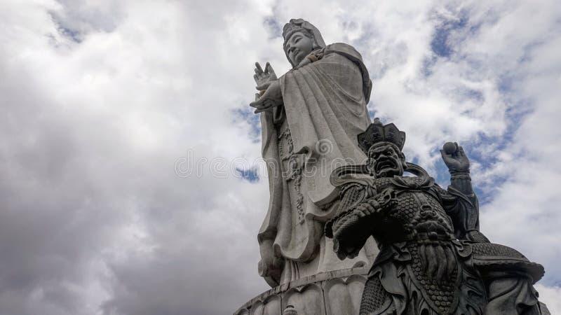 Buddhistische Skulptur gegen bewölkte Himmel stockfotos