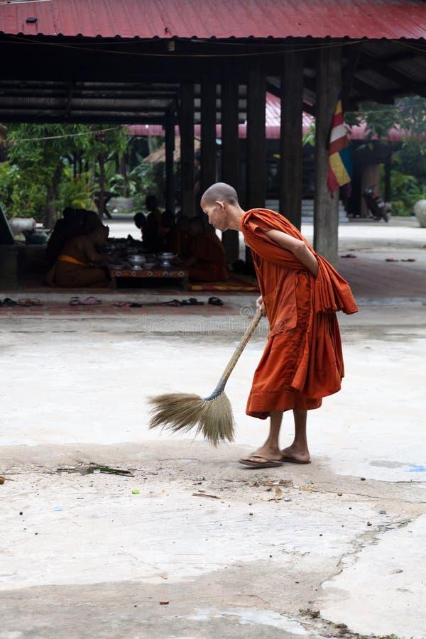 Buddhistischer Mönch, der draußen den Boden kehrt stockfotografie