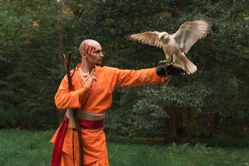 Buddhistischer Mönch mit einem Vogel auf seiner Hand im Wald stockbilder