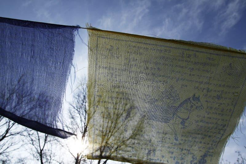 Buddhistisches tibetanisches Gebet kennzeichnet das Wellenartig bewegen in den Wind gegen blauen Himmel lizenzfreies stockbild