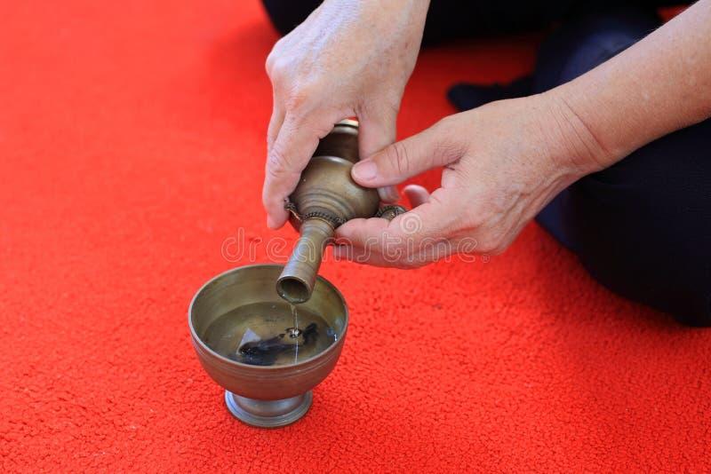 Buddist att hälla för gral bevattnar in i behållaren arkivbild